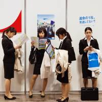 University students attend a job fair. Government figures show a record-high 98 percent of university graduates in Japan landed jobs at the beginning of this fiscal year. | BLOOMBERG