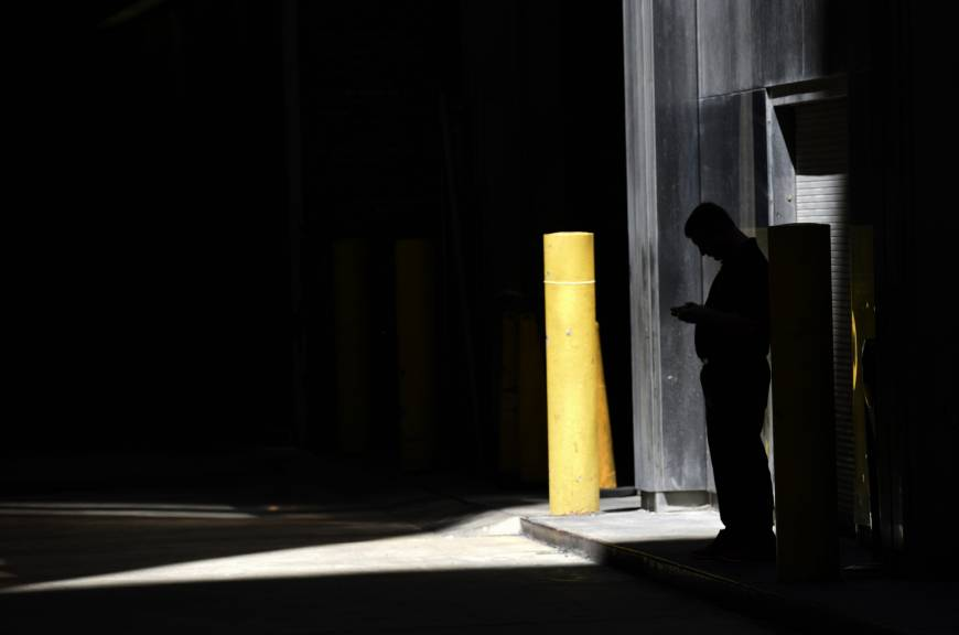 A man checks his phone in an alley in downtown Chicago last June. A security researcher says a website flaw at a U.S. company could have allowed anyone to pinpoint the location of nearly any cellphone in the United States. The lapse at LocationSmart, a company that gathers real-time data on cellular wireless devices, is the latest to highlight how little protection consumers have from trafficking in data about their location. | AP