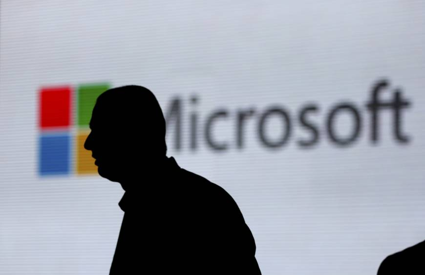 An unidentified man is silhouetted as he walks in front of Microsoft logo at an event in New Delhi last November. Microsoft says it's committing to giving users worldwide the same data and privacy rights being offered to Europeans under new regulations there. That means no matter where you live, you'll be able to see what Microsoft collects about you and correct or delete that information if necessary. | AP