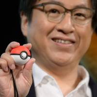 Shinya Takahashi, managing executive officer of Nintendo Co., holds a Poke Ball Plus controller during a news conference at which video games 'Pokemon: Let's Go Pikachu' and 'Pokemon: Let's Go Eevee' were unveiled in Tokyo on Wednesday. | BLOOMBERG