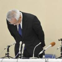 Suruga Bank President Akihiro Yoneyama (right) bows in apology during a news conference Tuesday in Numazu, Shizuoka Prefecture, to explain the fabrication of papers related to loans the bank extended to those who invested in share houses. | KYODO