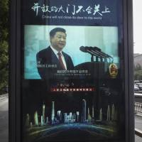 A man and vehicles pass by an electronic display panel advertising video footage of Chinese President Xi Jinping on a street in Beijing Thursday. China and Japan have both condemned the Trump administration's decision to launch an investigation into whether tariffs are needed on imports of vehicles and automotive parts into the United States. | AP