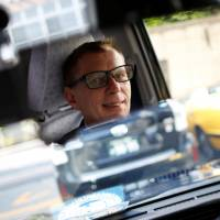 Austrian Wolfgang Loeger, a taxi driver for Hinomaru Kotsu Co., glances in his rearview mirror as he drives a JPN Taxi car, developed by Toyota Motor Co., in Tokyo on May 14. | REUTERS