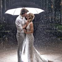 Hannibal and Emily Baldwin pose for a wedding photo Satureay under an umbrella outside the Casa Marina Resort in Key West, Florida. The Tampa couple had planned an outdoor wedding, but the evening ceremony and reception were moved inside due to rain bands emanating from Subtropical Storm Alberto. | BOB CARE / FLORIDA KEYS NEWS BUREAU / VIA AP
