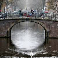 Cyclists cross a bridge in central Amsterdam last December. | REUTERS