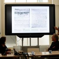 Researchers speak near a screen displaying pages of the diary of Anne Frank as the Anne Frank House publishes unknown text of the young Jew, then aged 13, who hid from the Nazis with her family in the Dutch capital, on Tuesday in Amsterdam. Two pages from her world-famous diary have been made visible with digital photo-editing techniques. | ANP / VIA AFP-JIJI