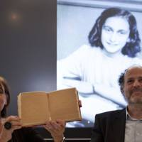 Teresien da Silva (left) and Ronald Leopold of the Anne Frank Foundation show a replica of Anne Frank's diary with two pages taped off during a news conference at the foundation's office in Amsterdam on Tuesday. | AP