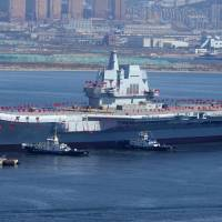 The 'Type 001A,' China's second aircraft carrier — and first indigenously built — is seen being transferred from a dry dock into the water at a shipyard in Dalian, in northeastern China's Liaoning province, on April 26. | AFP-JIJI