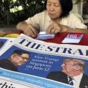 A news vendor counts her money near a stack of newspapers with a photo of U.S. President Donald Trump (right) and North Korea's leader Kim Jong Un on its front page in Singapore May 10. Weeks from his North Korea summit, President Donald Trump is staring down a dealmaker's worst nightmare: overpromising and underdelivering.