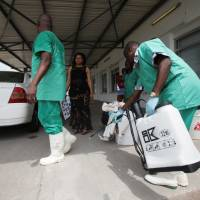A health worker sprays a colleague with disinfectant during a training session for Congolese health workers to deal with Ebola virus in Kinshasa in 2014. | REUTERS