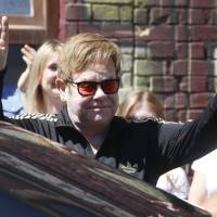 Elton John gestures to fans as he leaves a city market in Kiev Monday. John is in the Ukrainian capital for work on his AIDS foundation charity. | AP