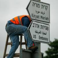 A new road sign indicating the way to the new US embassy in Jerusalem is set up on Monday. | AFP-JIJI