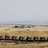 Israeli soldiers walk past tanks near the border with Syria in the Israeli-occupied Golan Heights, Israel, Friday. | REUTERS