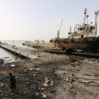 Workers inspect damage at the site of an airstrike on the maintenance hub at the Hodeida port, Yemen, Sunday. | REUTERS