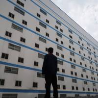 A worker poses outside a seven-story pig building of Guangxi Yangxiang's farm at Yaji Mountain Forest Park in Guangxi province, China, March 21. | REUTERS