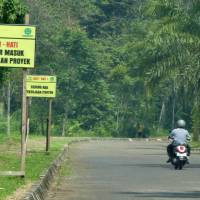 A motorcyclist rides past signs alerting drivers of heavy vehicles exiting and entering the construction site of a theme park, linked to companies with business interests tied to U.S. President Donald Trump, in Lido, Indonesia, in November. | AFP-JIJI