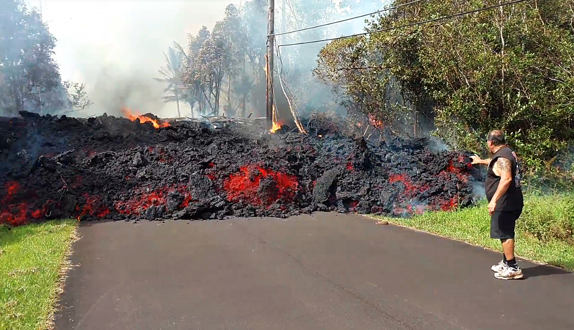 In this photo taken from video an unidentified man gets close to a lava flow advancing down a road in the Leilani Estates subdivision near Pahoa on the island of Hawaii Monday. Kilauea volcano has destroyed more than two dozen homes since it began spewing lava hundreds of feet into the air last week, and residents who evacuated don't know how long they might be displaced. The decimated homes were in the Leilani Estates subdivision, where molten rock, toxic gas and steam have been bursting through openings in the ground created by the volcano. | SCOTT WIGGERS / APAU HAWAII TOURS / VIA AP