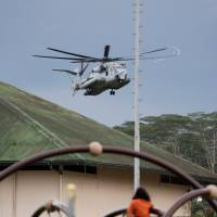 A U.S. Marine Corps helicopter lands in a field in Pahoa, Hawaii, Saturday. The helicopter, which practiced maneuvers in the area, stands by to evacuate residents in a Puna community, should molten rock or cracks in the ground block the escape route.   REUTERS