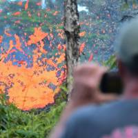 A man watches as lava issues from a fissure in the Leilani Estates subdivision near the town of Pahoa on Hawaii's Big Island on May 4 as up to 10,000 people were asked to leave their homes following the eruption of the Kilauea volcano that came after a series of recent earthquakes. | AFP-JIJI