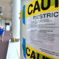 Warning and caution signs remain in front of the Hilo Downtown Post Office on Monday after it was closed due to fears of structural damage following the earthquakes on May 4 on Hawaii's Big Island. | AFP-JIJI