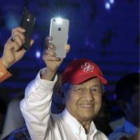 Former Malaysian strongman Mahathir Mohamad gestures with his smartphone as he waves to the crowd during an election campaign in Kuala Lumpur on Sunday.   AP