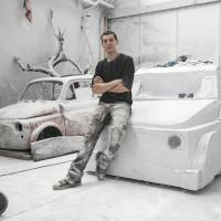 Italian artist sculpting iconic Fiat 500 car out of block of white marble
