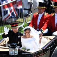 Britain's Prince Harry, the Duke of Sussex, and his wife, Meghan, the Duchess of Sussex, wave from the Ascot Landau Carriage during their carriage procession on the Long Walk as they head back toward Windsor Castle in Windsor on Saturday after their wedding ceremony. | AFP-JIJI