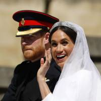 Britain's Prince Harry and his wife, Meghan, the Duke and Duchess of Sussex, wave from the Ascot Landau Carriage during a procession on Castle Hill outside Windsor Castle on Saturday after their wedding ceremony. | AFP-JIJI