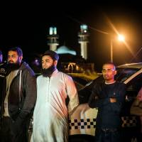 Residents and bystanders gather after they were asked to evacuate their homes when a device was found in the Imam Hussain Mosque on Sunday on the outskirts of Durban, South Africa. South African police bomb disposal units were on scene to verify the nature of the device. | AFP-JIJI