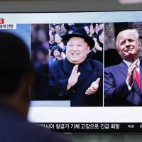 A man watches a news broadcast showing North Korean leader Kim Jong Un and U.S. President Donald Trump at Seoul Station on Wednesday.   AP
