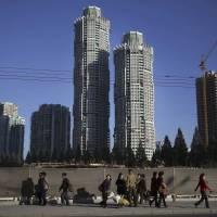 North Korean men and women walk past buildings under construction on Ryomyong Street in Pyongyang, where leader Kim Jong Un put his soldier-builders to work on yet another major project, in October 2016. | AP