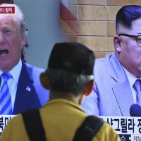 A man watches a TV screen showing file footage of U.S. President Donald Trump and North Korean leader Kim Jong Un during a news program at the main railway station in Seoul on Sunday. | AP