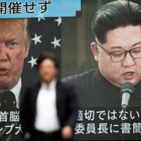 A pedestrian walks in front of a screen in Tokyo flashing a news report about U.S. President Donald Trump cancelling his meeting with North Korean leader Kim Jong Un. | AFP-JIJI