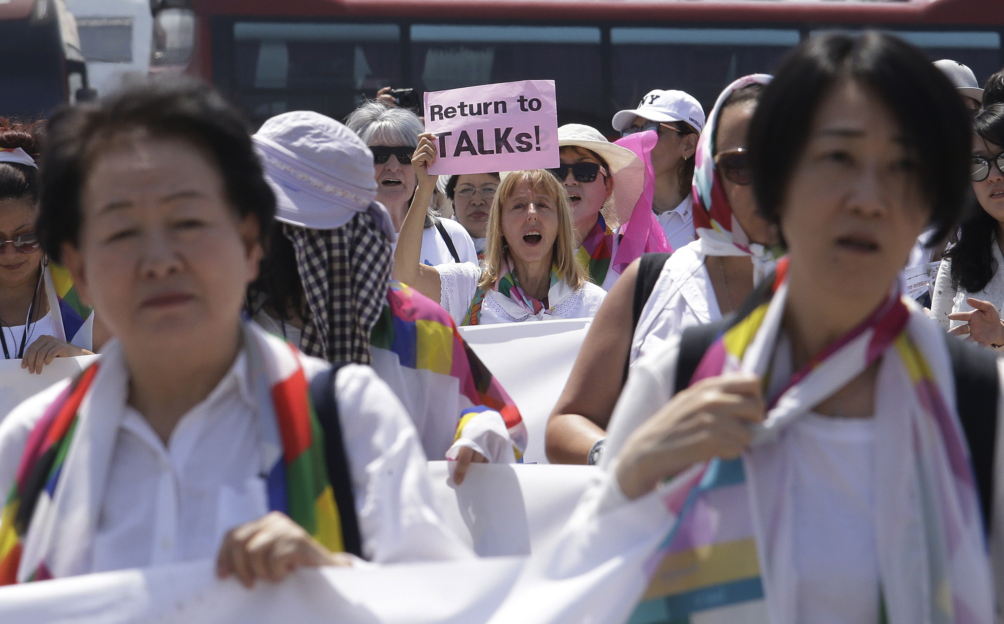 Female activists march toward the Unification Bridge, which leads to the border village of Panmunjom in the Demilitarized Zone, during the 2018 DMZ Women Peace Walk in Paju, South Korea, on Saturday. | AP
