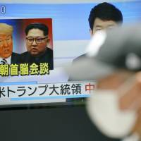 A man walks past a TV screen showing images of North Korean leader Kim Jong Un and U.S. President Donald Trump in Tokyo on Friday. | AP