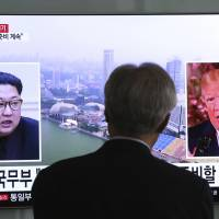 A man at Seoul Station watches a news broadcast featuring North Korean leader Kim Jong Un and U.S. President Donald Trump on Wednesday. | AP