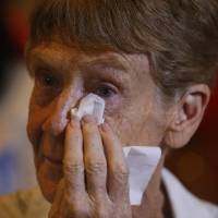 Australian nun Patricia Fox wipes away tears as supporters give her flowers Monday in Manila. | AP