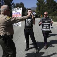 A Los Angeles County Sheriff's deputy asks protesters to stay on a sidewalk outside NASA's Jet Propulsion Laboratory before U.S. Vice President Mike Pence's visit to the laboratory Saturday in Pasadena, California. | AP