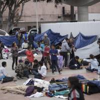 Migrants wait for access to request asylum in the U.S. at the El Chaparral port of Entry in Tijuana, Mexico, Monday. About 200 people in a caravan of Central American asylum seekers waited on the Mexican border with San Diego for a second straight day on Monday to turn themselves in to U.S. border inspectors, who said the nation's busiest crossing facility did not have enough space to accommodate them. | AP