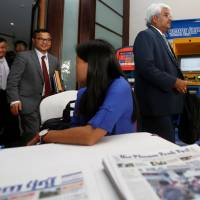 The Phnom Penh Post's new owner, Sivakumar Ganapathy (right), leaves after a news conference in Phnom Penh, Cambodia, on Friday. | REUTERS