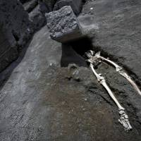 The legs of a skeleton emerge from the ground beneath a large rock believed to have crushed the victim's bust during the eruption of Mount Vesuvius in A.D. 79, at Pompeii's archeological site, near Naples, Italy, on Tuesday. | ANSA / VIA AP