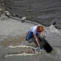 Anthropologist Valeria Amoretti works with a brush on the skeleton of a victim of the eruption of Mount Vesuvius in A.D. 79, which destroyed the ancient town of Pompeii, at the Pompeii archeological site, near Naples, Italy, on Tuesday. The skeleton was found during recent excavations and is believed to be of a 35-year-old man with a limp who was hit by a pyroclastic cloud during the eruption. | ANSA / VIA AP