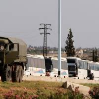 Buses carrying rebels who were evacuated from Rastan are seen in Homs countryside, Syria, Monday. | REUTERS