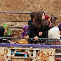 Syrians gather at a departure point prior to being evacuated from the rebel-held town of Rastan, in Syria's central Homs province, in a convoy of buses on Monday after rebels and civilians were granted safe passage to the rebel-held town of Jarabulus, in Aleppo province, following a new deal between rebel fighters and the government. | AFP-JIJI