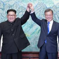 North Korean leader Kim Jong Un (left) and South Korean President Moon Jae-in raise their hands after signing on a joint statement at the border village of Panmunjom in the Demilitarized Zone in South Korea on April 27. | AP