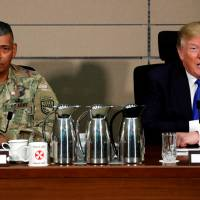 U.S. President Donald Trump delivers remarks before receiving a briefing from military commanders at Camp Humphreys in Pyeongtaek, South Korea, on Nov. 7. Beside him is Gen. Vincent Brooks. | REUTERS