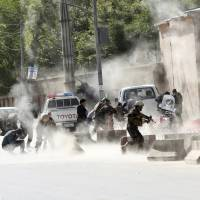 Security forces run from the site of a suicide attack after a second bombing in Kabul April 30. | AP