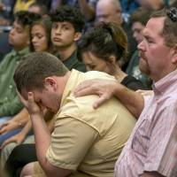Santa Fe High School student Aaron Chenowith is comforted by his father, Richard Chenowith, during a discussion about school shootings with Texas Gov. Greg Abbott at the Capitol Thursday in Austin, Texas. | JAY JANNER / AUSTIN AMERICAN-STATESMAN / VIA AP
