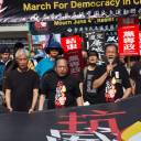 """Protesters hold a banner that reads """"March For Democracy in China"""" as they take part in a march in Hong Kong on Sunday to commemorate the June 4, 1989, Tiananmen Square crackdown in Beijing."""