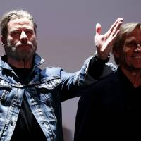 John Travolta and director Randal Kleiser arrive to attend a beach front cinema screening of the film 'Grease' in Cannes, France, Wednesday. | REUTERS